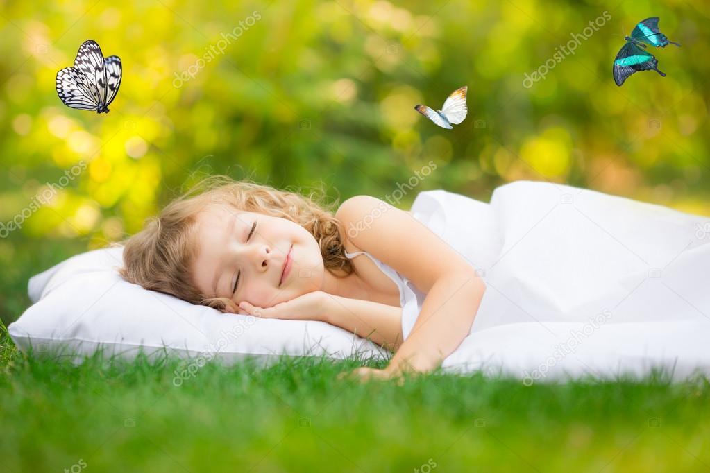 Kid sleeping in spring garden