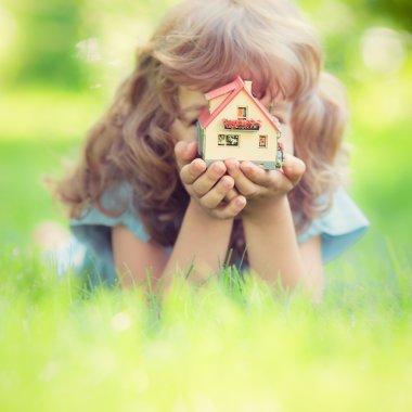 Child holding house
