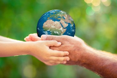 Child and senior holding Earth planet