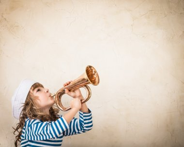 Child blowing  nautical horn.