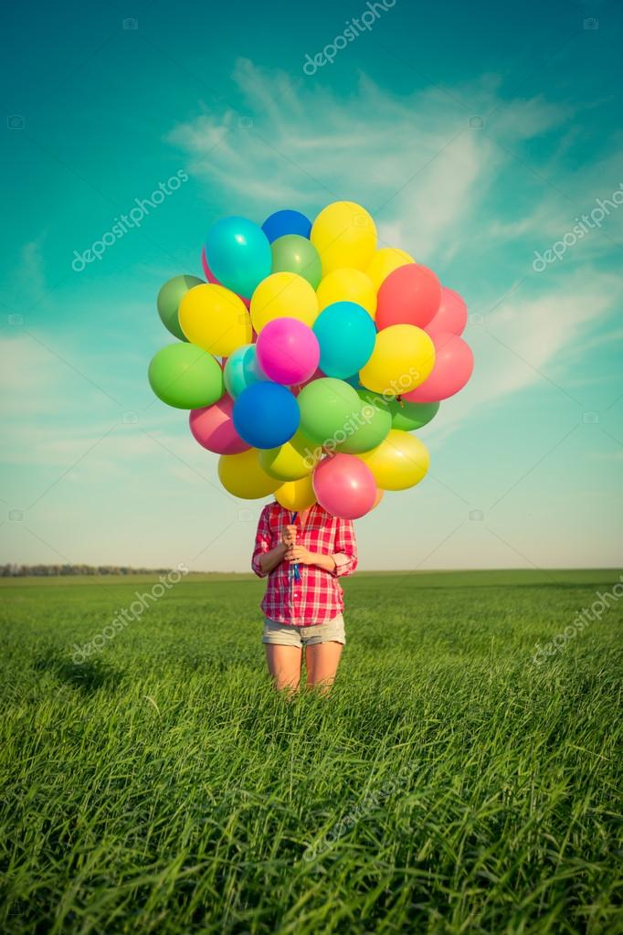 Woman with  balloons in  field