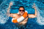 Junger Mann spielt im Schwimmbad