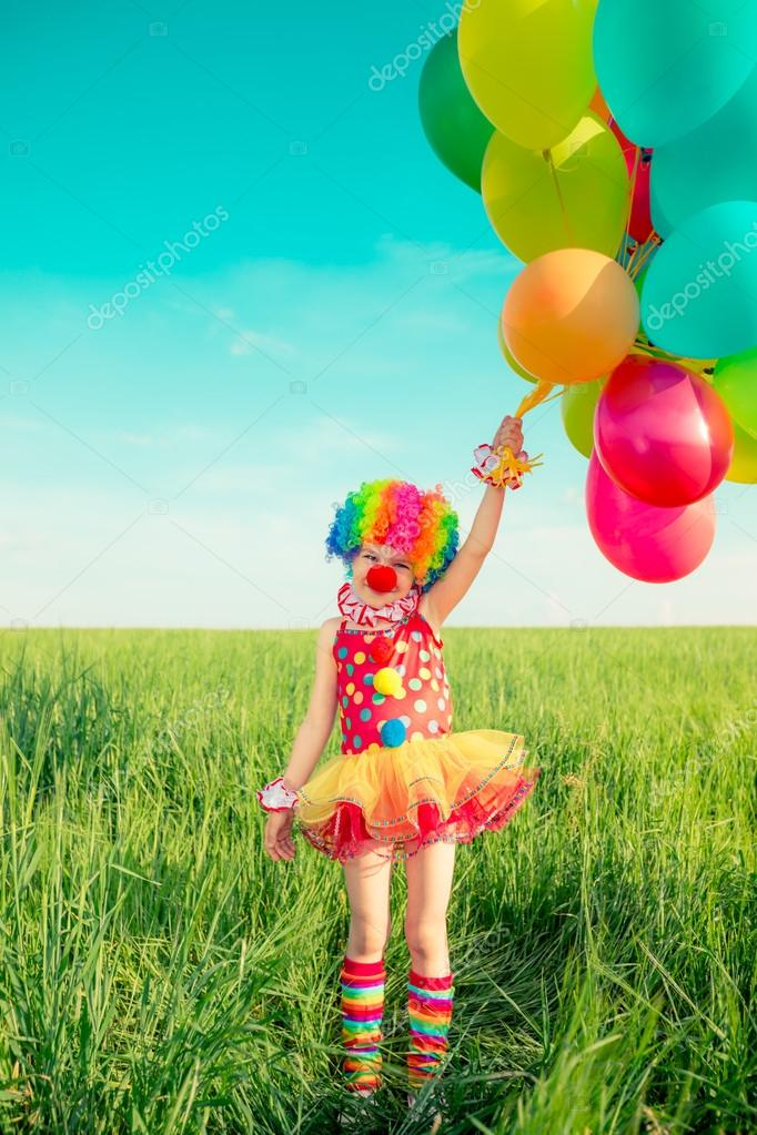 Child with balloons in spring field