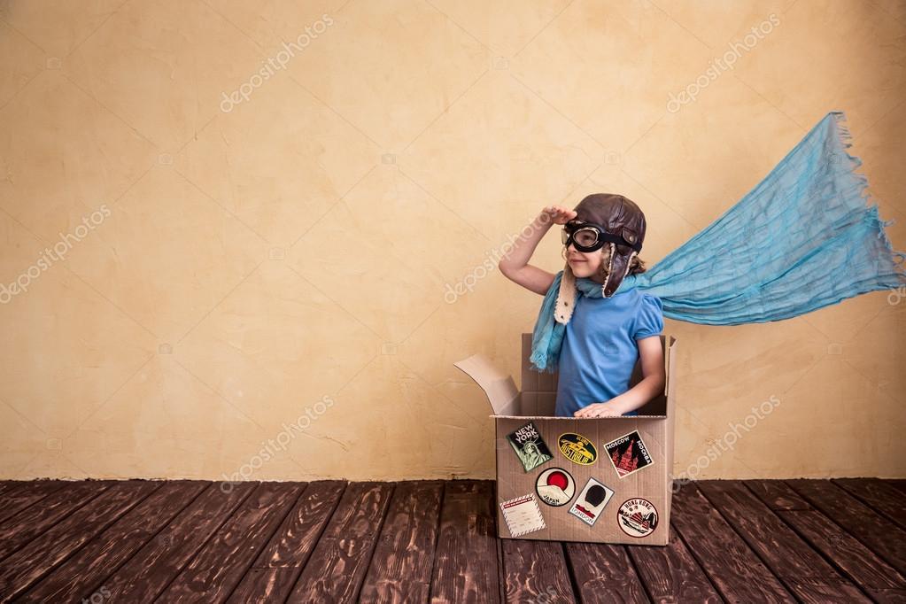 child playing in cardboard box