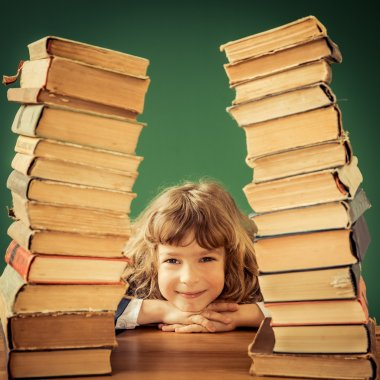 Happy child with stack of books