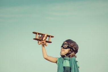 Happy child playing with toy airplane against summer sky background. Travel and vacation concept. Retro toned stock vector