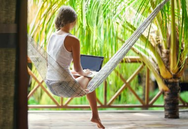 Woman in a hammock with laptop