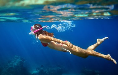 Woman swims underwater in tropical sea