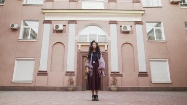 Mladý pěkný asijské žena staying near velký obytný apartments looking to camera