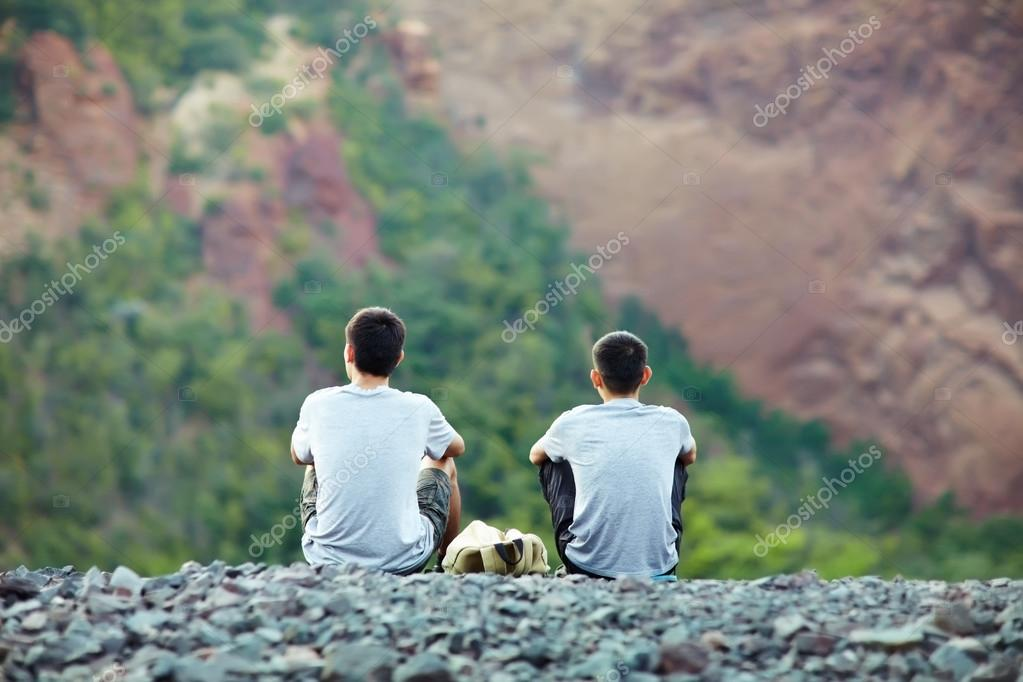 Two  men sitting on  cliff