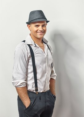 Handsome smiling man in hat and suspenders