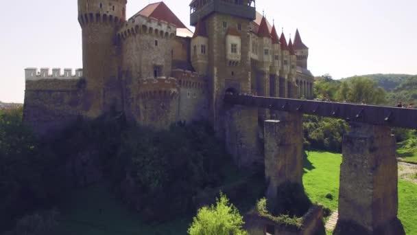 Zavřít pohled na středověký hrad s mostem, obklopený zeleným parkem