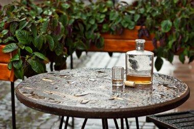 Boş bir masadaki bardağın yanında bir şişe alkol. Alkolizm, yalnızlık ve depresyon kavramı. Ahşap bir masada eski bir şişe. Masa yağmurdan ıslanmış..