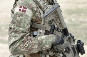 Soldier with assault rifle and flag of Denmark on military uniform. Collage.