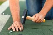 Pracovník ruce instalace asfaltové střešní šindele - horizontální plodin