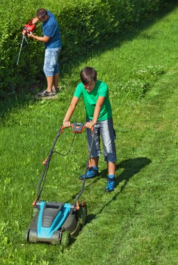Boy mowing the lawn while his father is trimming the hedge