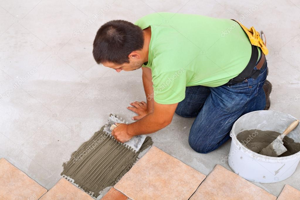 Man Laying Ceramic Tiles Floor Spreading The Adhesive Stock