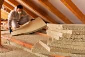 Muž položení vrstvy tepelné izolace pod střechou