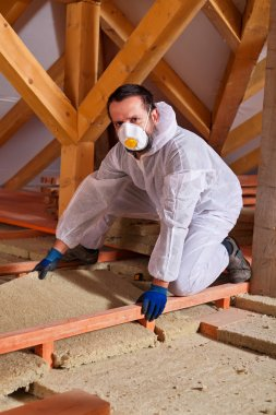 Man laying thermal insulation layer on building