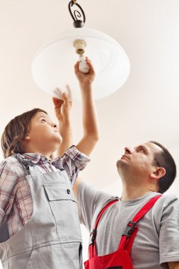 Father and son changing lightbulb in a ceiling lamp