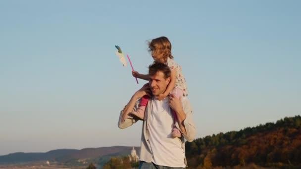 Rodinná dovolená v přírodě. Dcera sedí na zádech svého otce.