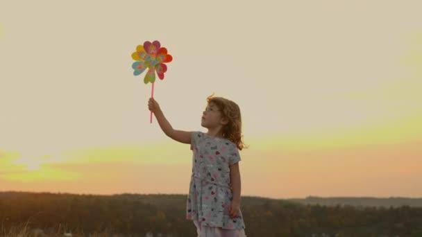 Egy kislány, aki a természeten áll naplementekor. Lány kezében játék szélmalom mozog a szélben.