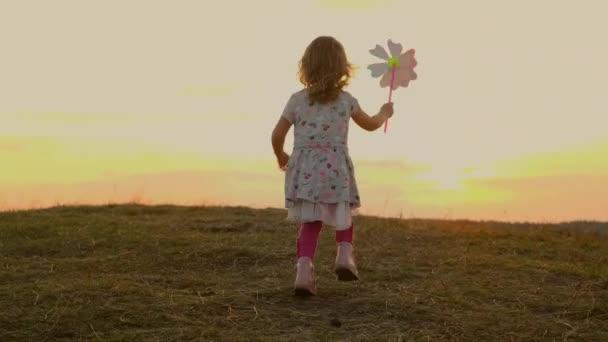 Holčička běží na přírodu při západu slunce. Dívka drží hračka větrný mlýn pohybující se ve větru.
