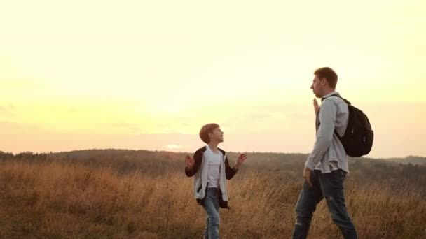 Walk In The Nature Of Dad And Son. Dad And Little Son Greet Each Other Clapping Their Hands