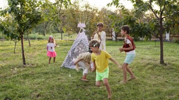 Öt gyerek játszik bekötött szemmel a kertben. Gyerekek az indiánok képében. Be van kötve a szeme..
