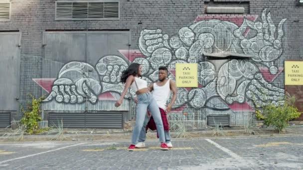 Street Dancing. Mladý pár tančí na ulici. Černoch a holka se pohybují rytmicky. Dělají stejné pohyby a usmívají se.