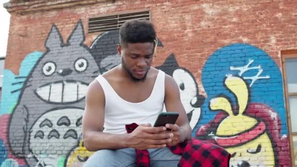 Mladý černoch s mobilním telefonem v rukou. Guy sedí na ulici s malovanými stěnami domů.