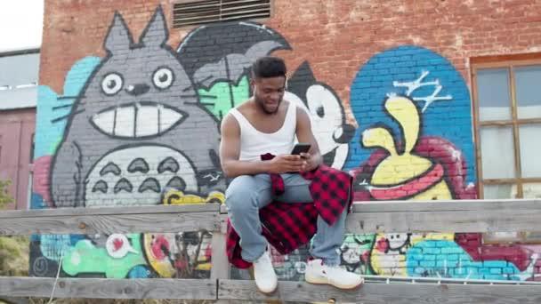 Fiatal fekete fickó mobiltelefonnal a kezében. Guy ül az utcán festett falak házak.