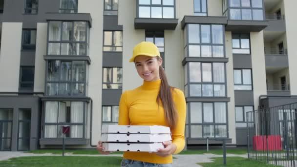 Mladá dívka pizza doručovatel stojící s krabicemi v rukou na ulici. Hezká bruneta ve žluté čepici a svetru.