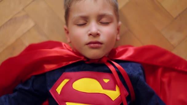 Superman öltönyös kisfiú csukott szemmel fekszik a földön. Kinyitja a szemét.