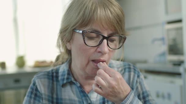 Žena vlaštovky pilulky a pije vodu, zatímco sedí ve své kuchyni.