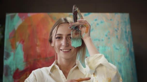 Fiatal lány tartja közel az arc ecset mártott festék.