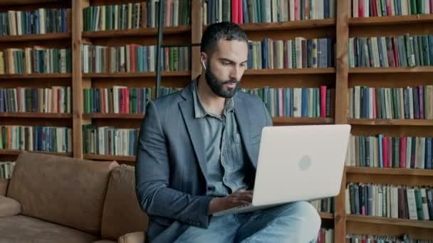 Laptopot használó fiatalember a könyvtárban.