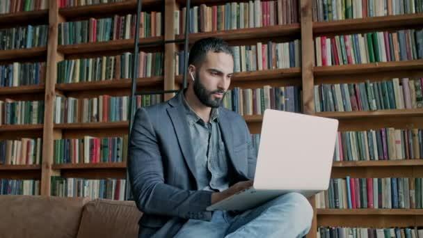 Stílusos sötét hajú fickó Laptop a szobában sok könyvet.