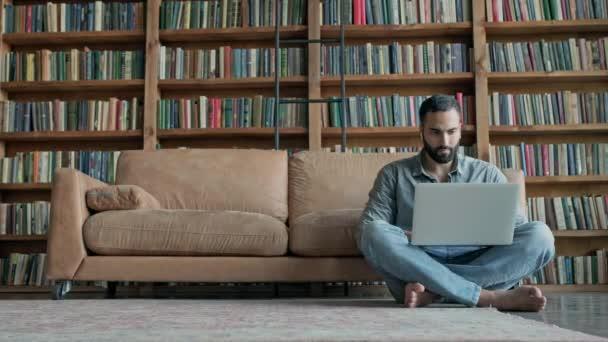 Stílusos fiatalember ül a padlón laptoppal.