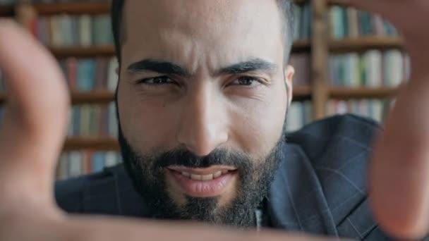 Mladý muž z Blízkého východu v knihovně dělá náměstí s rukama jako rám a dívá se na to.