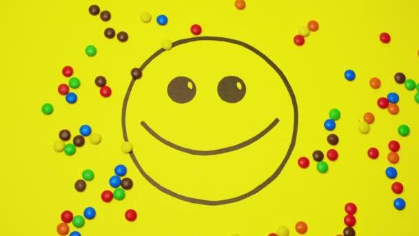 Smiley na žlutém pozadí naplněném barevnými bonbóny. Kulaté bonbóny pryč od obrázku.