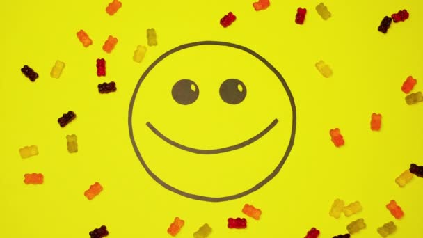 Smiley na žlutém pozadí plněné barevnými bonbóny.