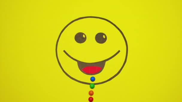 Smiley On Yellow Background Filled With Colored Candies.