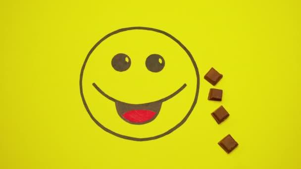 Smiley na žlutém pozadí. Kousky čokolády pohybovat kolem něj.