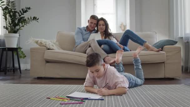 Chlapec leží na podlaze v místnosti a kreslí na kus papíru. Na gauči Mladí rodiče.