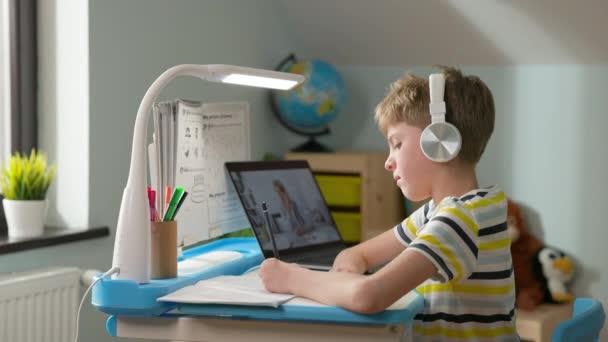 Chlapec sedí doma u laptopu. Online lekce. Chlapec pozdravuje učitele online. Mává svou rukou..