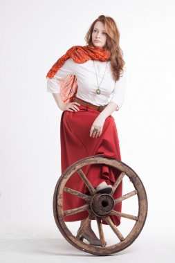 Woman in long red skirt  standing near wheel of the cart