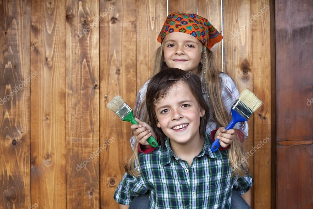 Happy kids repainting the wood shed