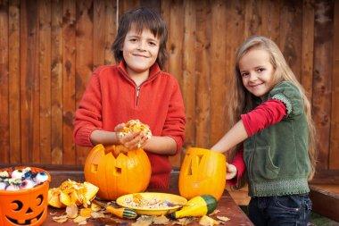 Kids carving their pumpkin jack-o-lanterns