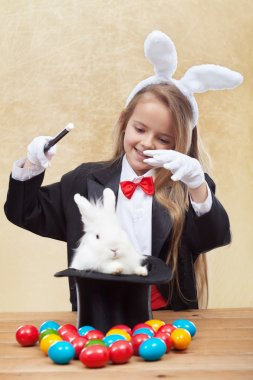 Happy magician girl conjuring up the easter bunny and eggs